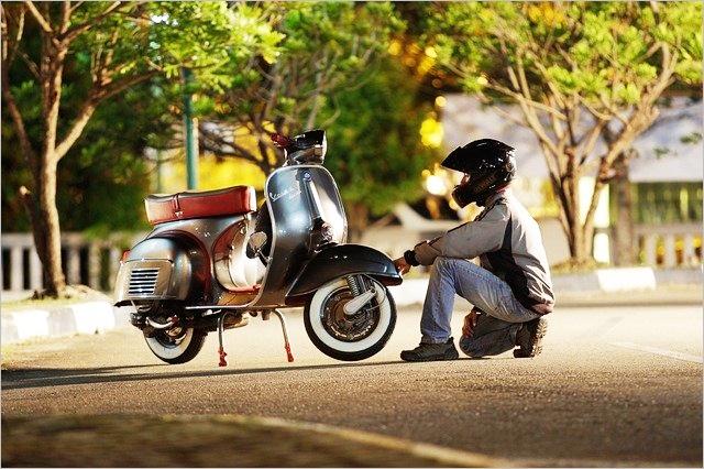 バイクにお別れしている風の青年